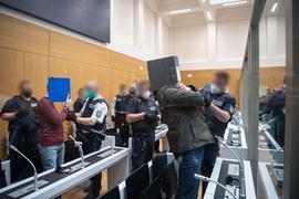 """Die Angeklagten werden von Justizbeamten kurz vor Beginn des Prozesses gegen die rechtsterroristische Vereinigung """"Gruppe S."""" in einen Saal im Oberlandesgericht Stuttgart-Stammheim geführt."""
