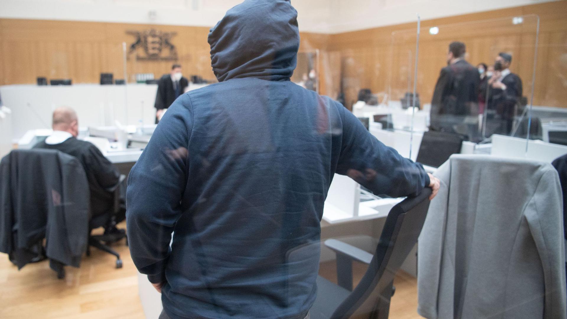 """Ein Prozessteilnehmer mit einer Kapuze  kommt kurz vor Beginn des Prozesses gegen die rechtsterroristische Vereinigung  """"Gruppe S."""" im Oberlandesgericht Stuttgart-Stammheim."""