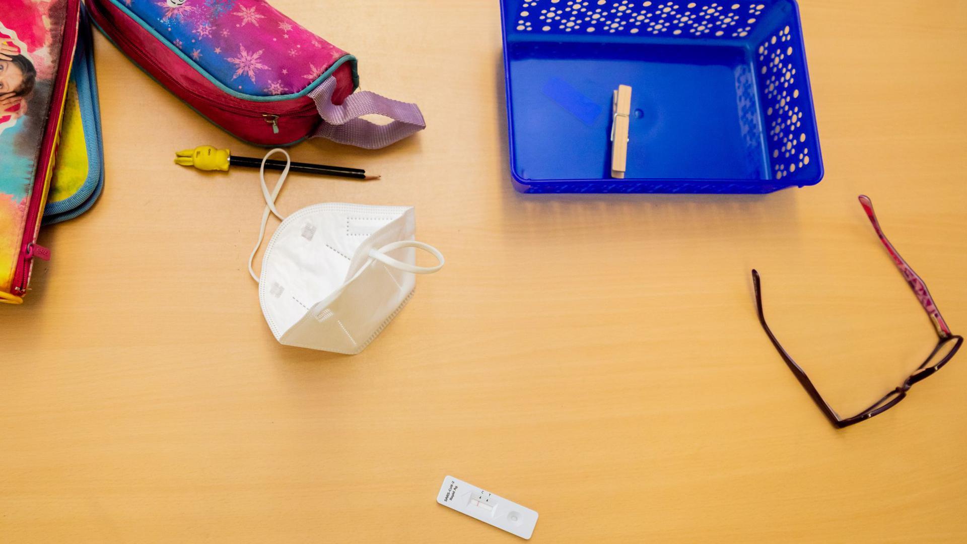 Ein Schnelltest, eine FFP2-Maske sowie andere Utensilien liegen bei einem Probelauf mit Corona-Schnelltests auf einem Schultisch.