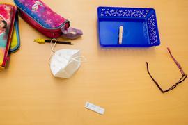 Ein Schnelltest, eine FFP2-Maske sowie andere Utensilien liegen bei einem Probelauf mit Corona-Schnelltests an der Grundschule in der Köllnischen Heide in Berlin-Neukölln auf einem Schultisch.