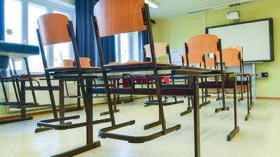In einem leeren Unterrichtsraum an einer Schule sind die Stühle auf einen Tisch gestellt.