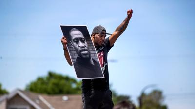 Tony L. Clark hält ein Foto des verstorbenen George Floyd. Der ehemalige Polizist Derek Chauvin ist des Mordes schulig gesprochen worden.