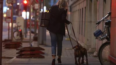 Eine Frau in Düsseldorf geht am Abend mit ihren Hunden spazieren.