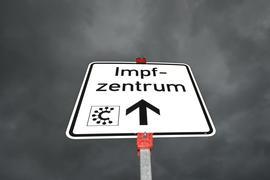 Ein Hinweisschild zeigt die Richtung zu einem Impfzentrum.