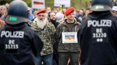"""Zwei Demonstranten stehen mit einem Schild - """"Veteranen für Recht und Freiheit"""" - auf der Straße des 17. Juni in Berlin."""