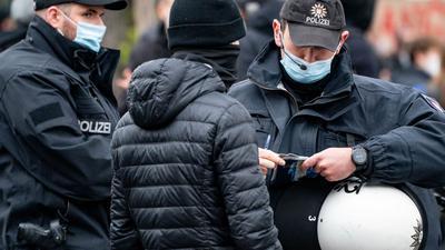 Polizisten kontrollieren die Personalien von einem Teilnehmer einer Demonstration in Hamburg.