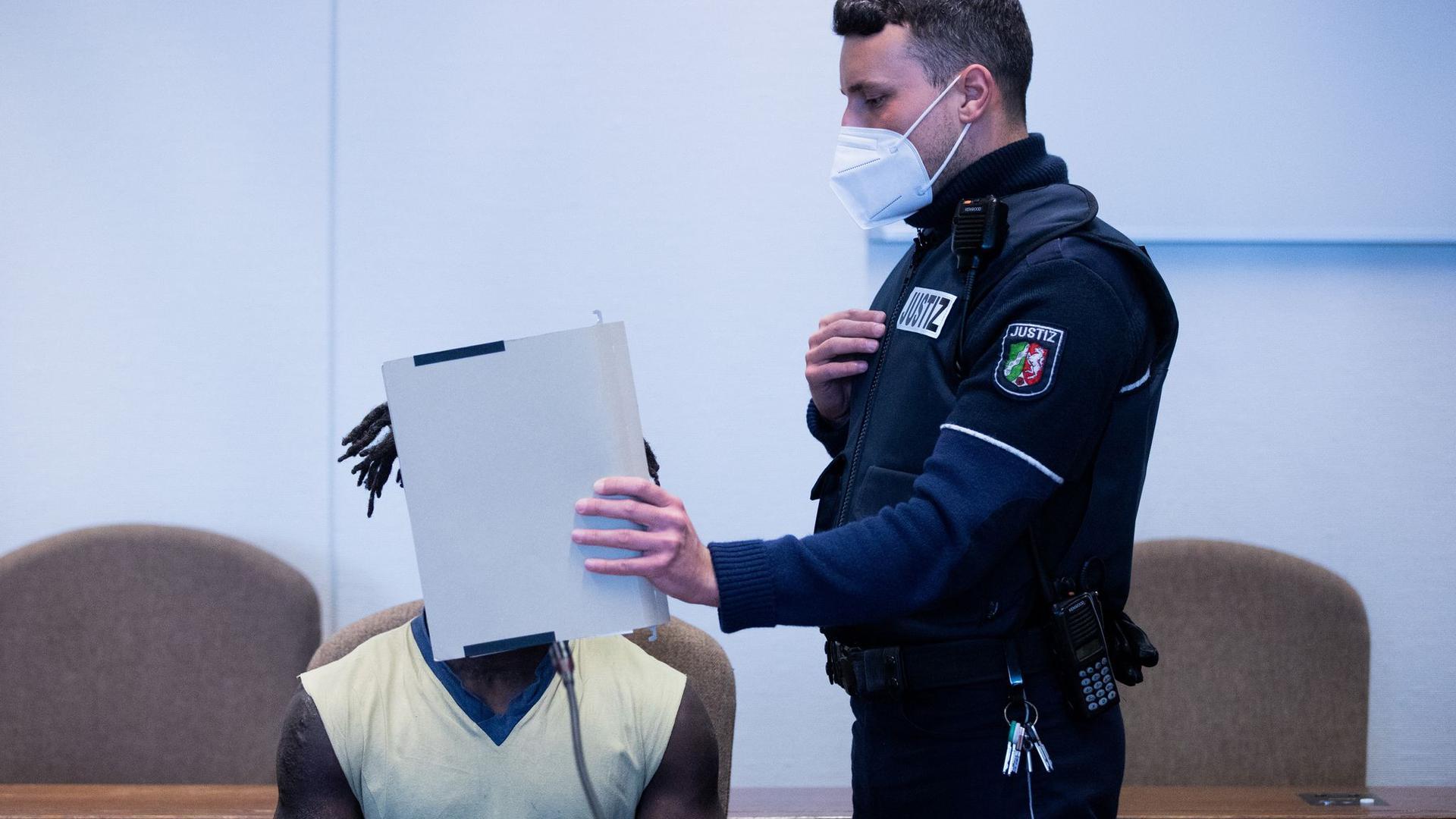 Der Angeklagte wird in Handschellen in einen Gerichtssaal im Landgericht Köln geführt.