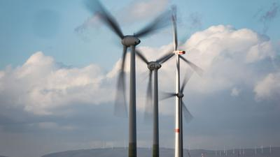 Windräder drehen sich auf einer Anhöhe in Rheinhessen.