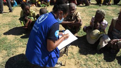 Eine Mitarbeiterin des Welternährungsprogramms spricht mit einigen Ältesten einer Gemeinde auf Madagaskar über ihre Situation.