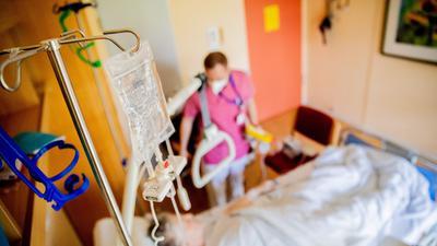 Ein Infusionsbeutel hängt auf der Viszeralchirurgie-Station des Krankenhauses Havelhöhe über einem Patientenbett.
