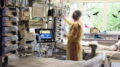 Ein Fachkrankenpfleger auf einer Intensivstation, auf der an Covid-19 erkrankte Patienten behandelt werden.