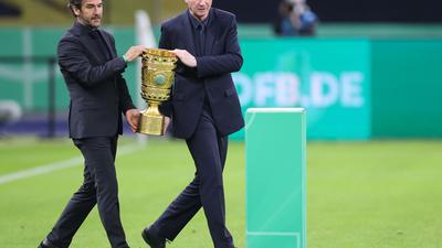 Karl-Heinz Riedle (l) und Perry Bräutigam tragen den DFB-Pokal auf das Feld.