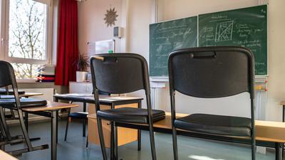 Hochgestellte Stühle in einem leeren Klassenzimmer einer Gesamtschule.