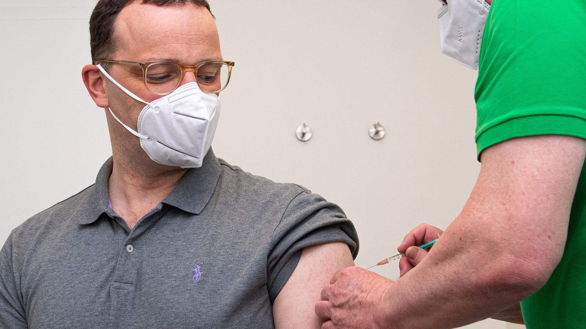 Jens Spahn (l,CDU), Bundesminister für Gesundheit, wird in einer Hausarztpraxis mit dem Impfstoff AstraZeneca geimpft.
