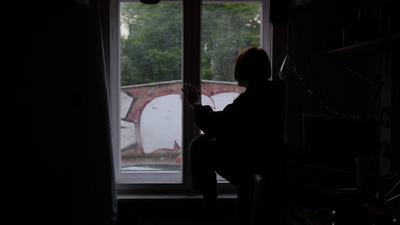 Eine Jugendliche sitzt in einem abgedunkelten Zimmer am Fenster.