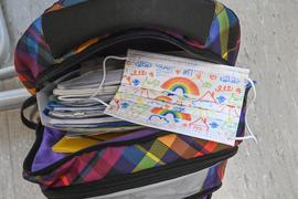 Eine Maske liegt auf dem Rucksack eines Grundschülers. Immer mehr Bundesländer kehren zum Regelunterricht zurück.