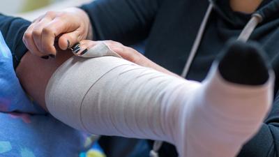 Eine Pflegeschülerin übt das Anlegen eines Thrombose-Verbandes.