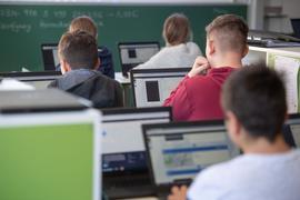 Schülerinnen und Schüler einer 9. Klasse arbeiten im Unterricht an Laptops.