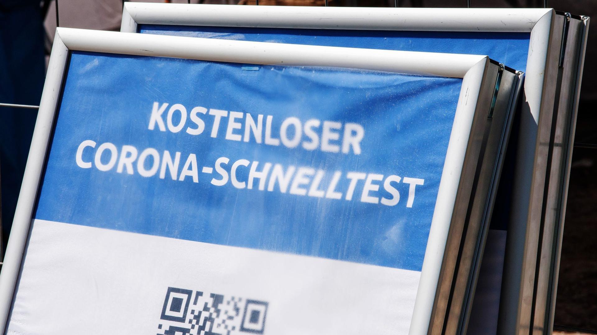 """Ein Schild mit der Aufschrift """"Kostenloser Corona-Schnelltest"""" steht vor einem Testzentrum in München. Die Sieben-Tage-Inzidenz in Deutschland ist laut RKI den zweiten Tag in Folge gestiegen."""