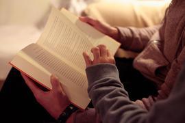 Eine Mutter liest ihrer Tochter aus einem Buch vor.