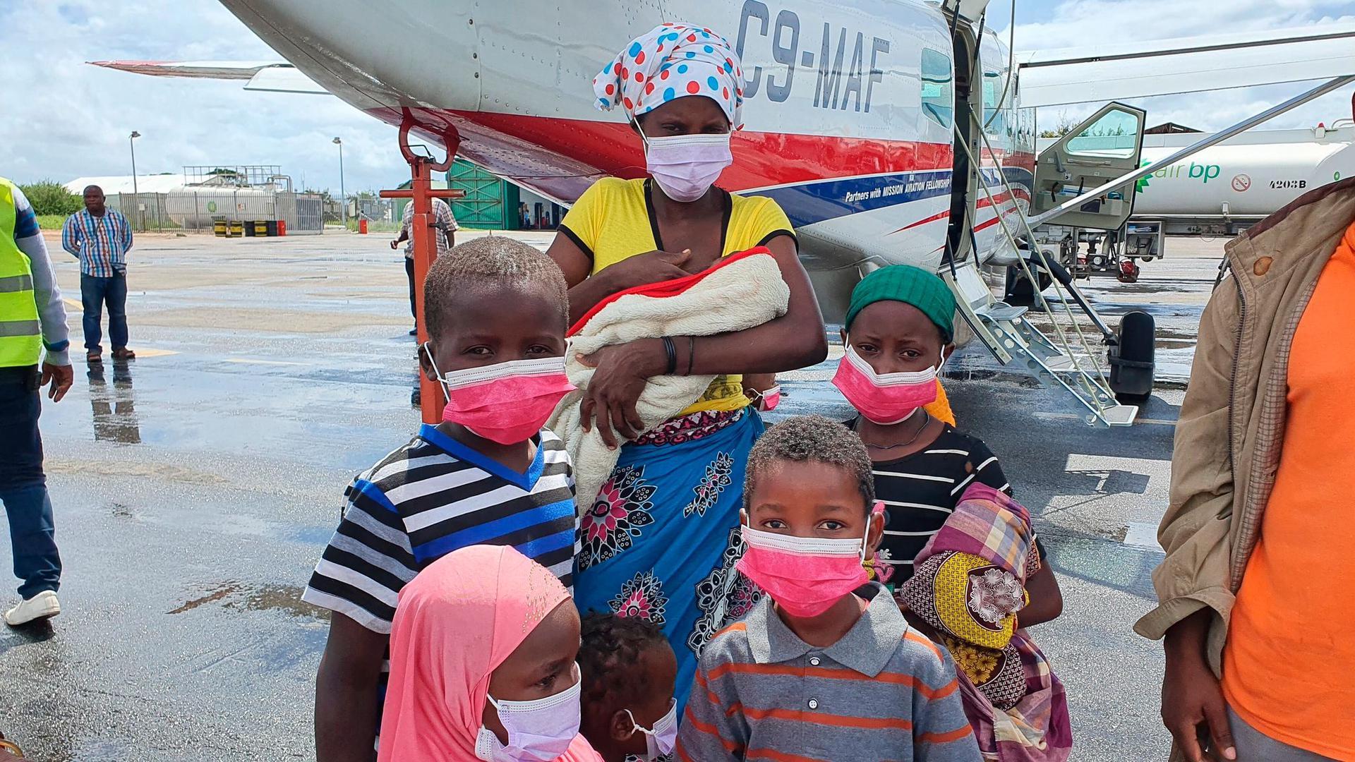 Eine Familie steht auf dem Rollfeld des Flughafens der Provinzhauptstadt Pemba, nachdem sie evakuiert wurden. In der Provinz Cabo Delgado verüben islamistische Rebellen seit 2017 immer wieder brutale Attacken. Nach Angaben des Welternährungsprogramms (WFP) sind in der Region fast eine Million Menschen infolge von Terror und Gewalt vom Hunger bedroht.