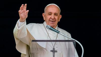 Papst Franziskus winkt aus dem Fenster seines Arbeitszimmers mit Blick auf den Petersplatz einer Menge von Gläubigen und Pilgern zu.
