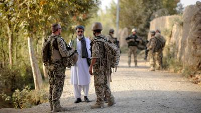 Ein Bundeswehrsoldat (l) und ein Dolmetscher (r) sprechen nahe Kundus im Distrikt von Char Darreh mit einem Mann.