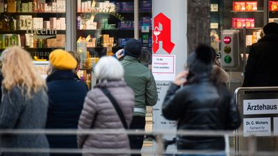 Passanten stehen Schlange vor einer Apotheke. Der von Apotheken ausgestellte digitale Impfnachweis ist eine freiwillige Ergänzung des weiter gültigen gelben Impfheftes aus Papier.