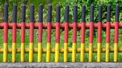 Ein in den Farben der Deutschlandfahne angestrichener Gartenzaun. Einer Studie zufolge haben sich in Deutschland zwei verfestigte Lager mit extrem gegensätzlichen Haltungen gebildet.