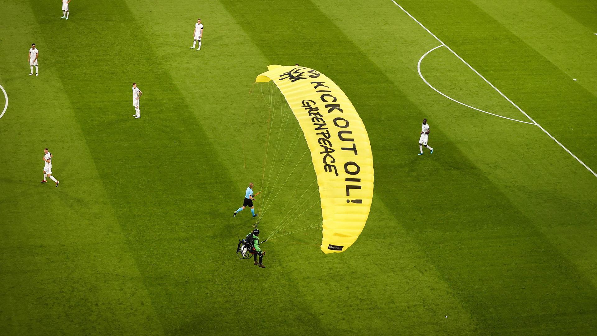Ein Greenpeace-Aktivist landet mit einem Motorschirm-Flieger bei einer Protestaktion auf dem Spielfeld.