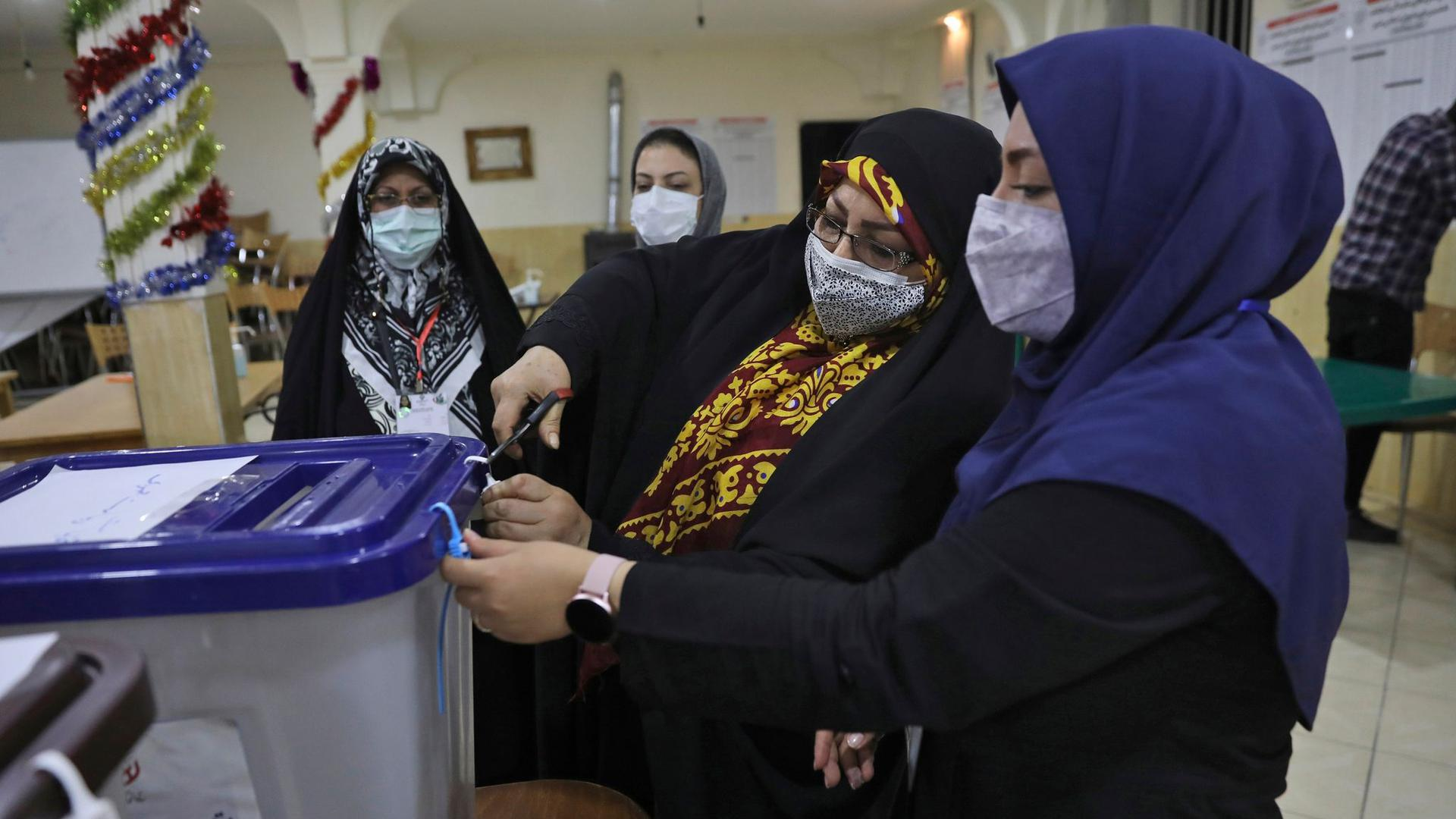 Wahlhelferinnen öffnen eine Urne in einem Wahllokal in Teheran.