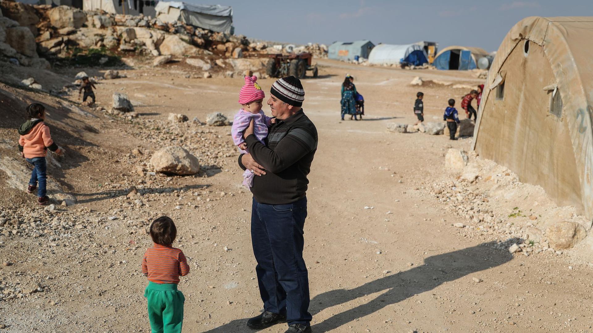 Ein Mann steht mit seinen Kindern in einem Flüchtlingslager in der Provinz Idlib.