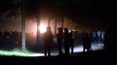 Behelmte Polizisten stehen am Rande der Stadtpark-Wiese und werden von einem Lichtmast angestrahlt. Die Polizei hat eine Party mit rund 3000 Menschen im Hamburger Stadtpark aufgelöst.