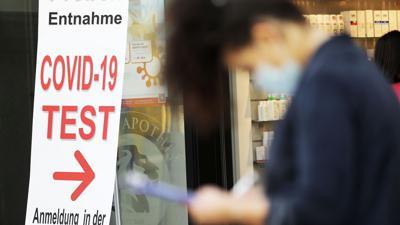 Eine Frau füllt vor einer Apotheke in Bonn ein Formular für einen Covid-19-Test aus.