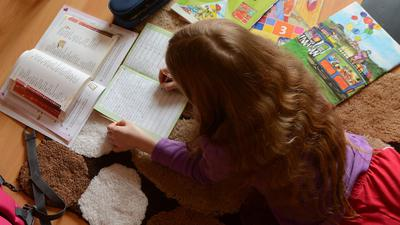 Ein Mädchen liegt auf einem Teppich in seinem Kinderzimmer und erledigt seine Hausaufgaben im Fach Deutsch.