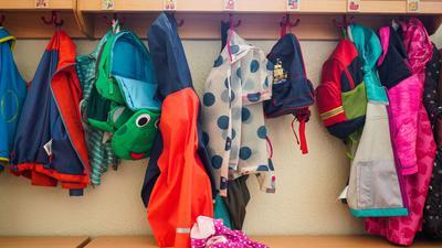 Jacken und Rucksäcke hängen an der Garderobe einer Kita. (Symbolbild)