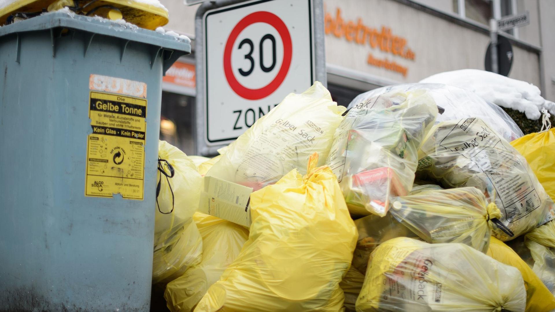 Mülltonnen und gelbe Säcke mit Kunststoff-Abfällen stapeln sich auf einem Fußweg.