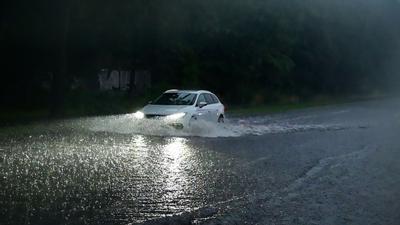 Ein Auto fährt durch die überflutete  Gladbacher Straße in Krefeld.