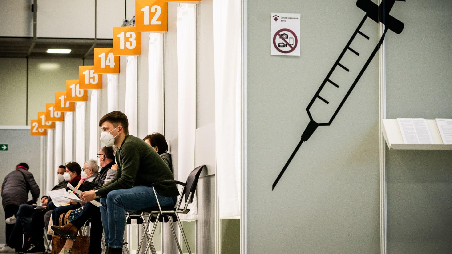 Menschen warten im Corona-Impfzentrum auf dem Berliner Messegelände auf ihre Impfung. Mehrere Politiker fordern eine Strafe für Impfterminschwänzer.
