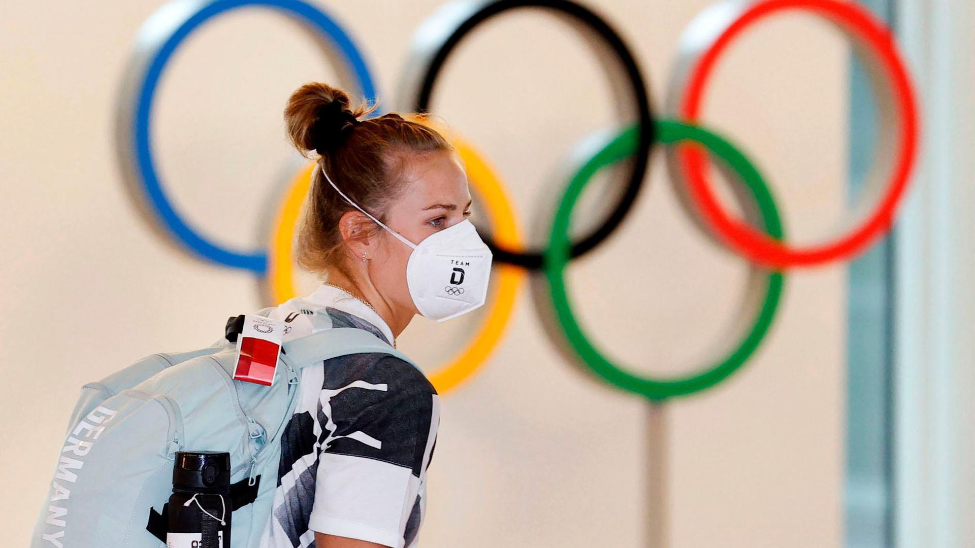 Eine deutsche Athletin trägt eine Schutzmaske und geht bei ihrer Ankunft am Flughafen Haneda an den Olympischen Ringen vorbei.