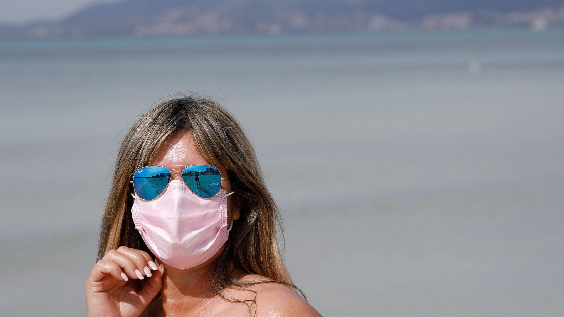 Maske am Strand: Auch 2021 steht der Sommerurlaub - wie hier auf Mallorca - ganz im Zeichen der Pandemie.