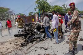 Sicherheitskräfte und Zivilisten stehen in der Nähe eines Autowracks nach dem ersten Anschlag im somalischen Mogadischu. Die islamistische Terrormiliz Al-Shabaab hat nun sechs weitere Mörsergeschosse abgefeuert.