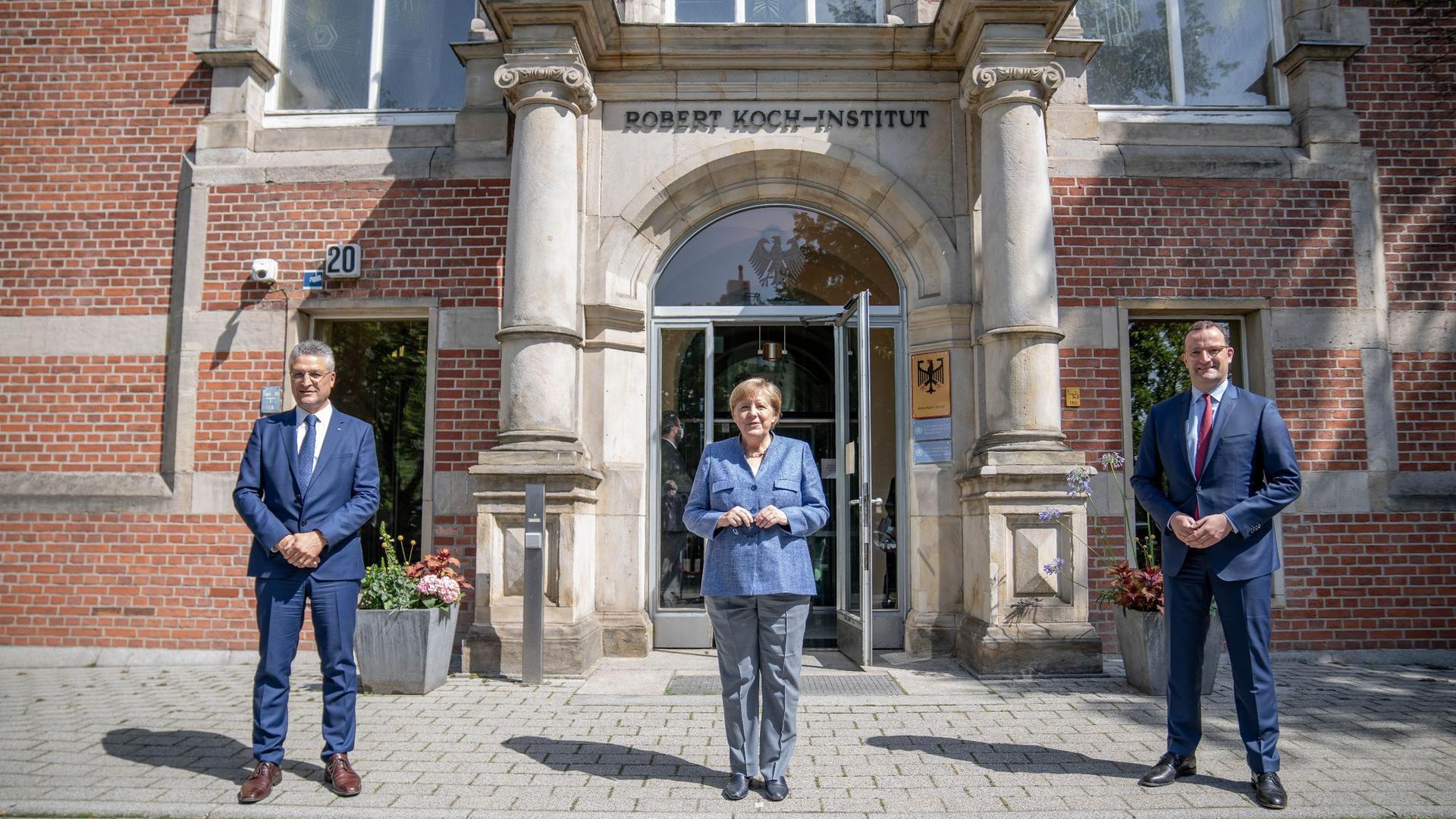 RKI-Präsident Lothar Wieler, Bundeskanzlerin Angela Merkel und Bundesgesundheitsminister Jens Spahn vor dem Eingang zum Robert Koch-Institut.