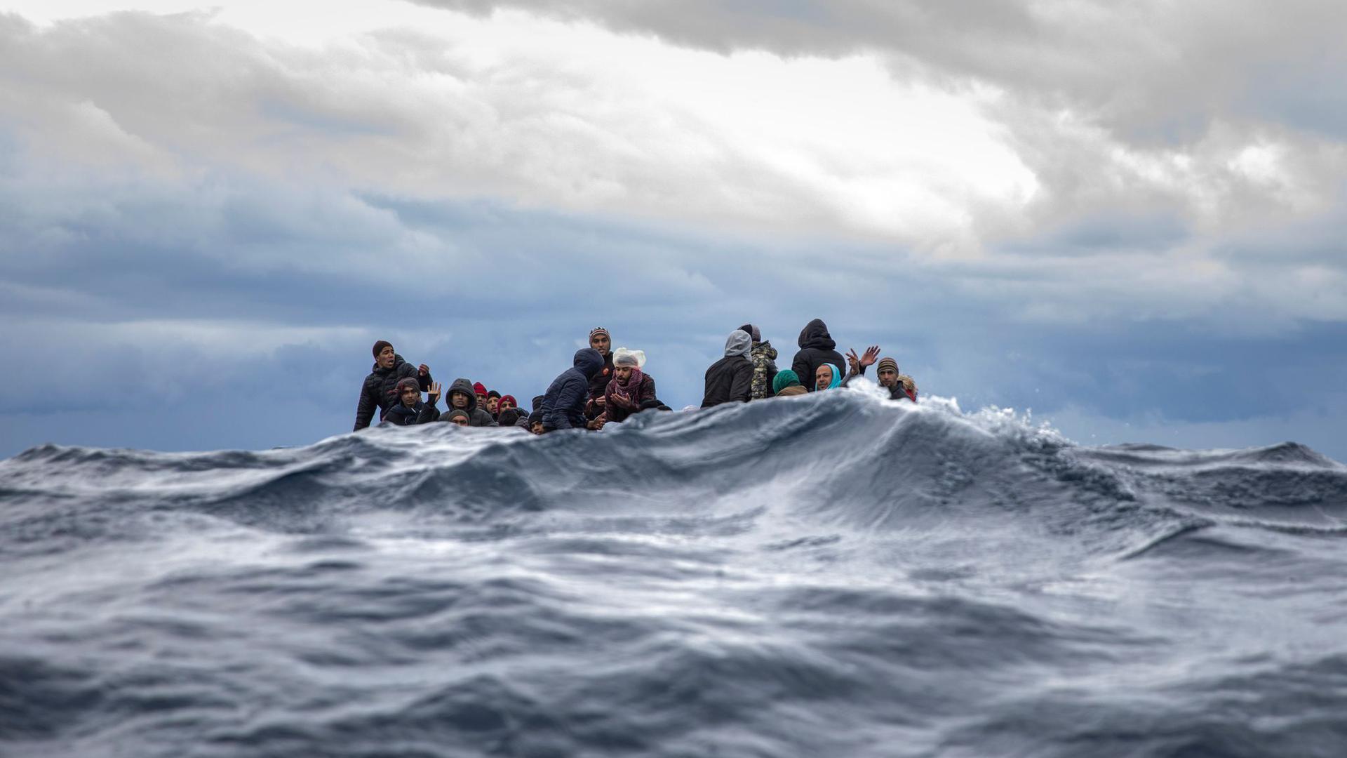 Männer aus Marokko und Bangladesch sitzen in einem überfüllten Holzboot im Mittelmeer vor der Küste von Libyen.