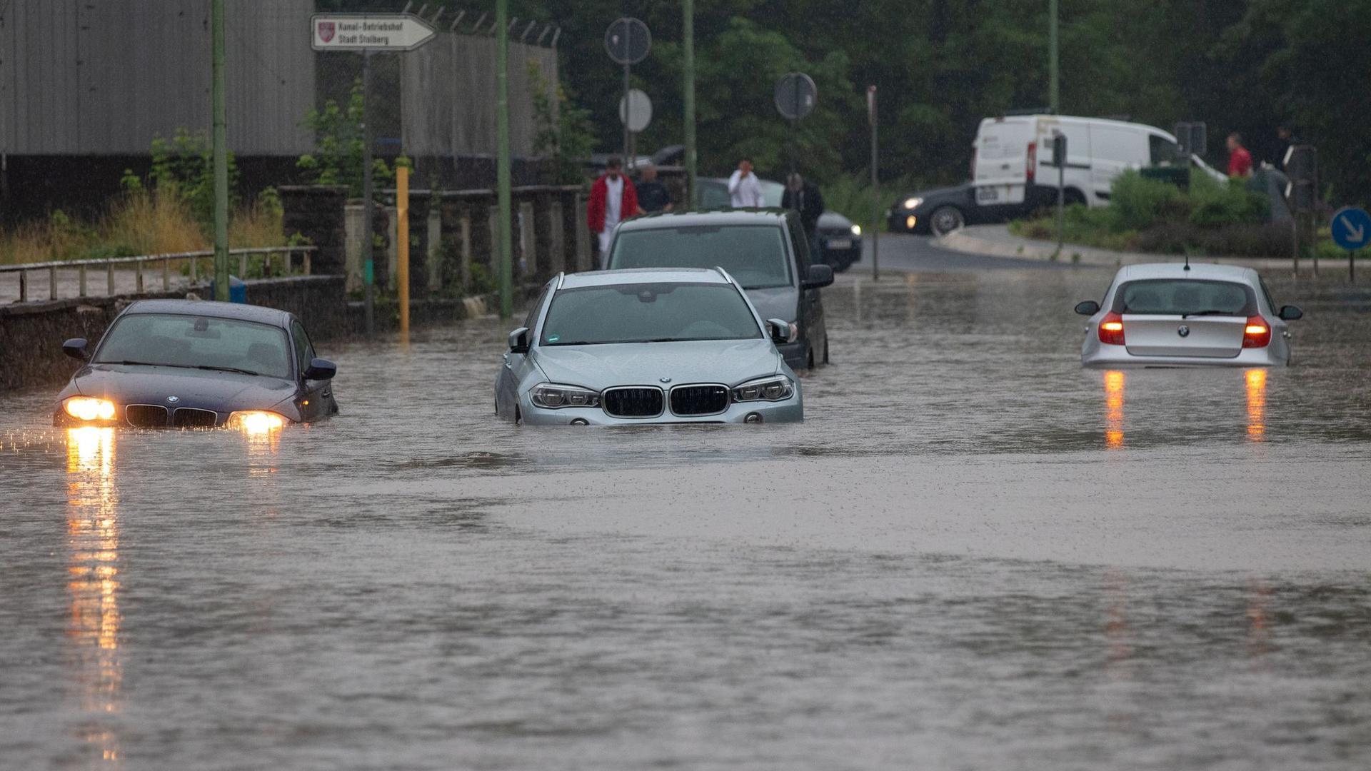 Mehrere Autos stecken nach Starkregen auf einer überfluteten Straße in Stolberg in NRW fest. Der Bach Vicht war über die Ufer getreten.