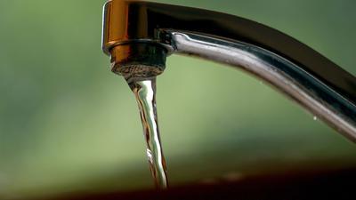 Leitungswasser fließt aus einem Wasserhahn. Legionellen können unter anderem über Wasserhähne übertragen werden.