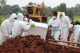 Arbeiter bereiten einen Sarg für eine Beerdigung auf dem speziellen Corona-Abschnitt eines Friedhofs in Indonesien vor.