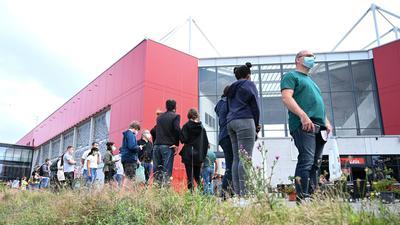 Menschen stehen vor dem Stadion des Fußball-Bundesligisten Mainz 05 Schlange für die Corona-Impfung.