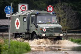 Ein Sanitätsfahrzeug der Bundeswehr fährt über eine überflutete Straße.