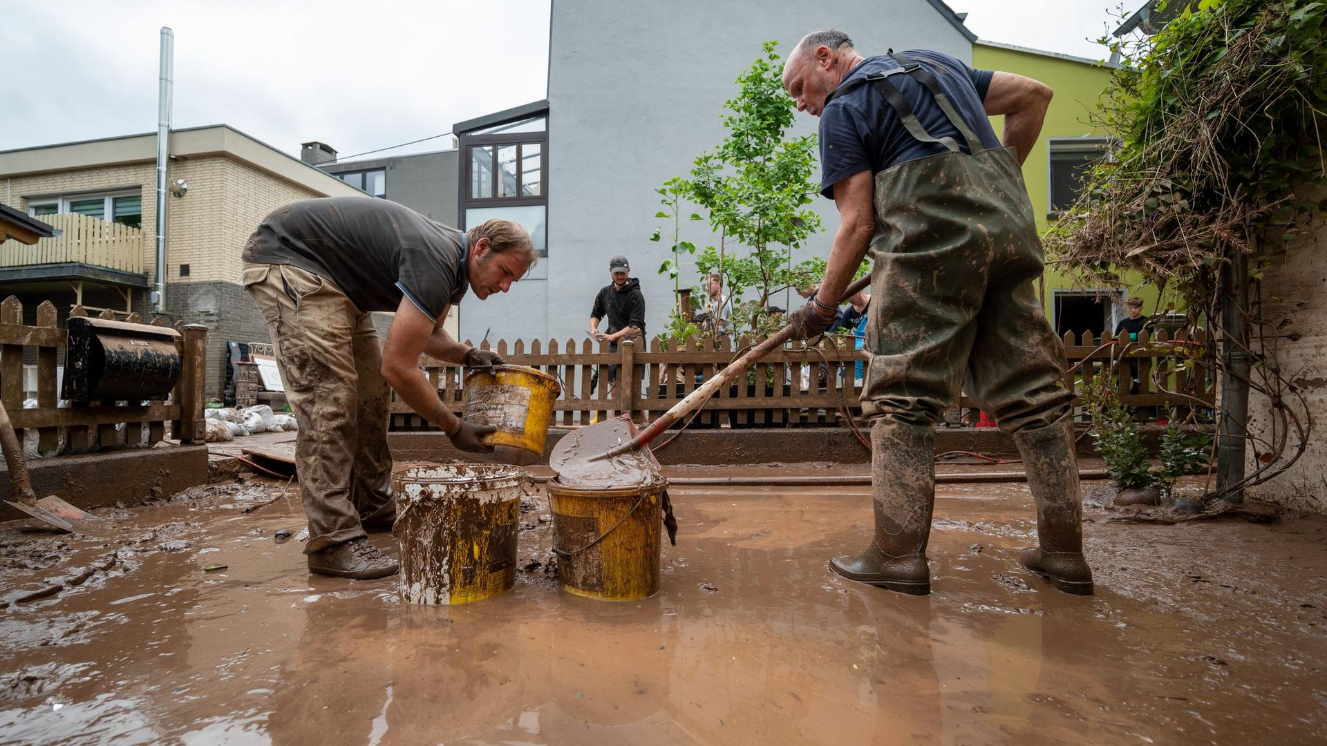 Mit Eimern entsorgen Anwohner die Schlammmassen nach dem Hochwasser der Kyll. Zahlreiche Häuser im Ort waren betroffen, Menschen mussten in Sicherheit gebracht werden.